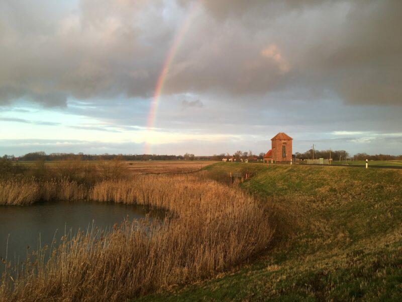 Regenbogen und Sonnenuntergang am Polder-Deich nahe Penkefitz